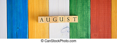 Wide view image of wooden cubes spelling the word August