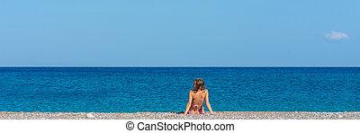 Wide view image of young woman in pink bikini sunbathing