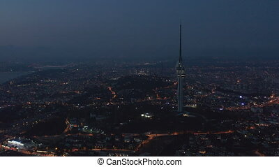 Wide View of Huge New TV Tower of Istanbul with Mosque on Hill in Background at Night, Aerial Drone Shot