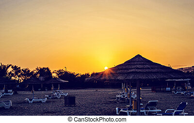 Wide view to yellow sunset above beach
