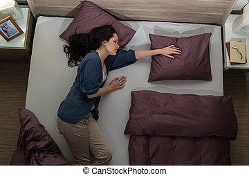 Widow lying in bed missing her husband - Young widow lying...