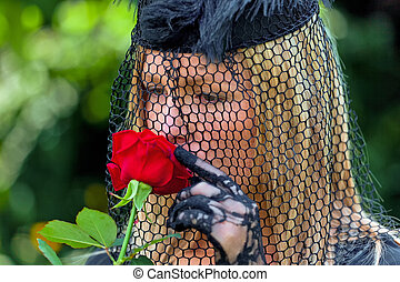 a young, grieving widow with a veil and rose. death and inheritance.