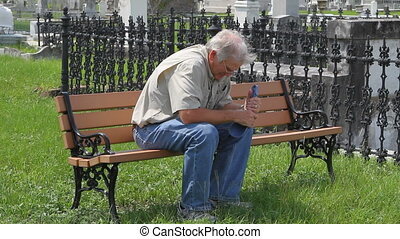 Widower sits wringing his hat as he mourns the death of his wife on a bench in the cemetery.