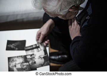 Widower watching pictures - Sad widower watching pictures...