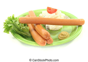 Wiener Sausage with potato salad and lettuce on a white...