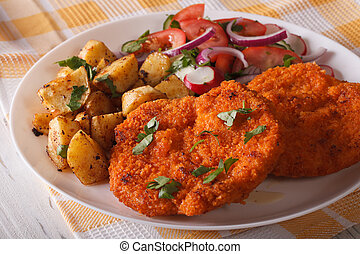 Wiener schnitzel, fried potatoes and vegetable salad closeup. Horizontal