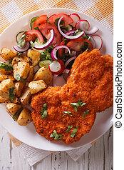 Wiener schnitzel, fried potatoes and salad closeup. vertical top view