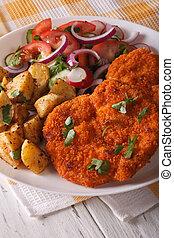Wiener schnitzel, fried potatoes and vegetable salad closeup. vertical