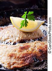 wiener schnitzel frying in a pan