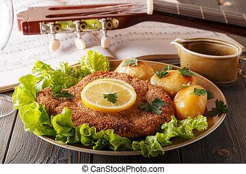 Wiener schnitzel with potatoes and salad.