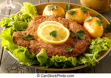 Wiener schnitzel with potatoes and salad.