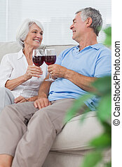 Wife and husband clinking their glasses of red wine sitting ...