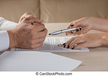 Wife and husband signing divorce documents, woman returning wedding ring