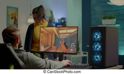 Wife arguing with man gamer during space shooter videogame tournament playing on RGB powerful personal computer. Pro cyber player performing video games streaming from home at online championship