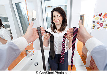 Wife choosing a tie for man