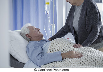 Wife covering husband with blanket