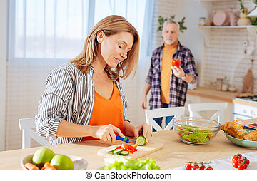 Wife cutting vegetables for salad and talking to her husband