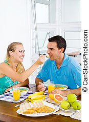 wife feeding breakfast to husband