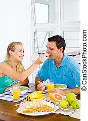 wife feeding breakfast to husband