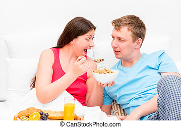 wife feeding her husband breakfast in bed