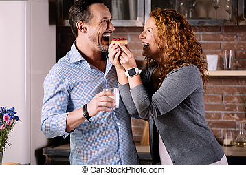Wife feeding husband with cake