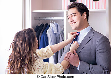 Wife helping husband to get dressed up
