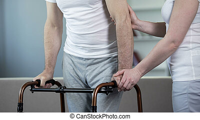 Wife helping ill senior husband to move with walking frame, rehabilitation