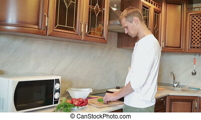 wife hugging her husband while he cutting vegetables for salad on the kitchen