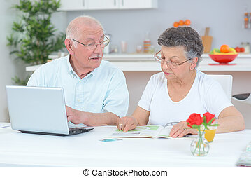 Wife looking at magazine, husband on laptop