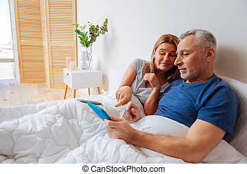 Wife showing the best option for husband shopping online