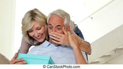 Wife surprising her husband with gift