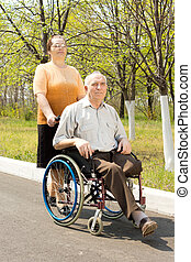 Wife taking her disabled husband for a walk