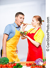 wife treats a man with fresh vegetable salad, a pair of aprons in the kitchen