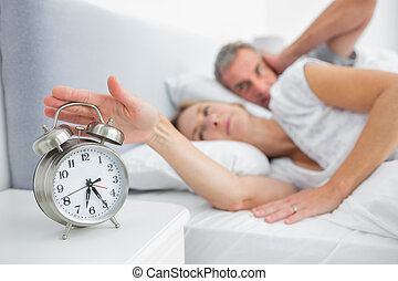 Wife turning off alarm clock as husband is covering ears