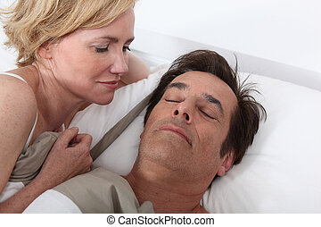 Wife watching husband sleeping