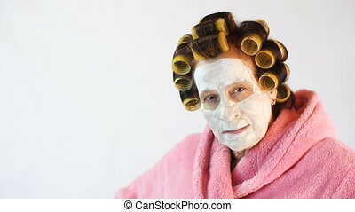 Wife with a cosmetic mask and curlers