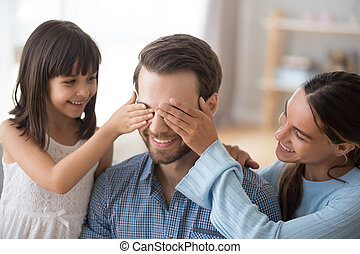 Wife with kid closing eyes of smiling daddy make surprise
