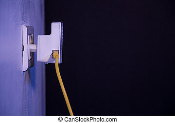 WiFi extender in electrical socket on the wall with ethernet cable plugged in