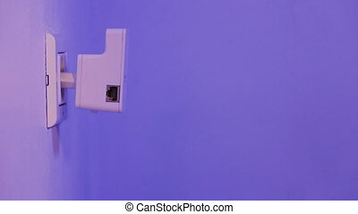 WiFi repeater in electrical socket on the wall. Device that...