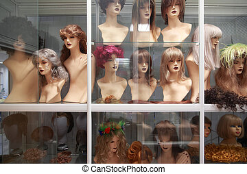 Wigs on mannequins, rows of wigs on white shelves behind glass