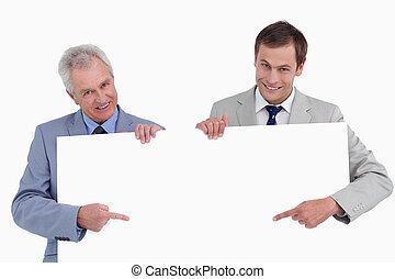 wijzende, handen, hun, meldingsbord, het glimlachen, leeg, tradesmen