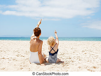 wijzende, moeder, op, achter, kind, gezien, strand, zanderig