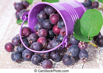 Wild berries spill out of the bucket on an old wooden board
