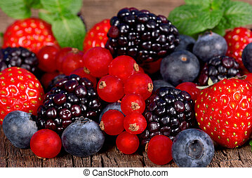 Wild berries - Fresh berries with mint leaves on a wooden...