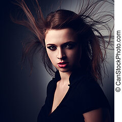 Wild expressive young woman with wind hairstyle and vamp look on dark. Closeup portrait