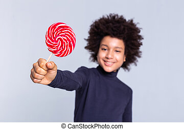 Resolute dark-haired joyful boy pulling out hand with candy in it