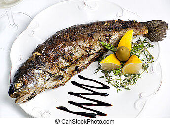 trout grilled on a plate with lemon