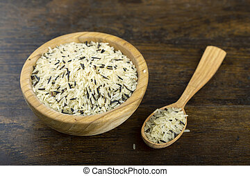 Wild rice in a wooden bowl on a wooden table.