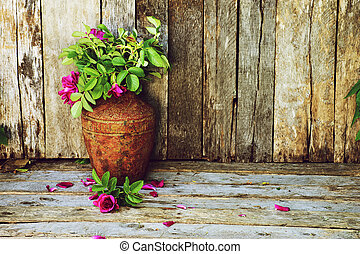 Richly colored vintage style image of beautiful wild roses in a rustic vase on a grunge wood backdrop with copy space.