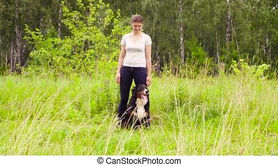 Woman posing with bernese shepherd dog - Wild shot. Woman...